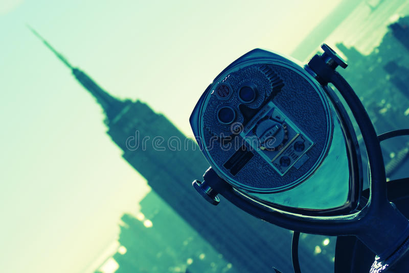 Binoculars and Empire State Building. Binoculars on the top of the rock rockefeller centre pointing towards the Empire State Building CP royalty free stock image