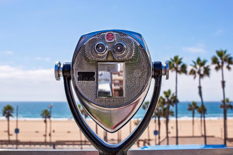 Binoculars looking out over a beach and ocean. Binoculars looking out over a beach with palm trees and the ocean. Travel or vacation concept stock photography