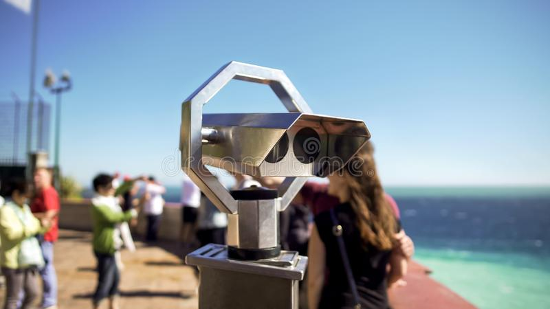 Binoculars at observation deck on sunny day, people on background looking at sea. Stock photo stock image