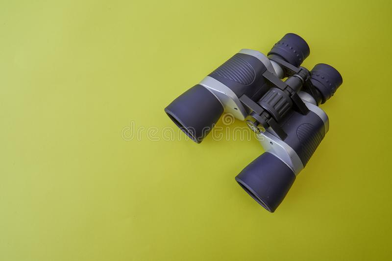 Binoculars silver and gray on yellow background royalty free stock image