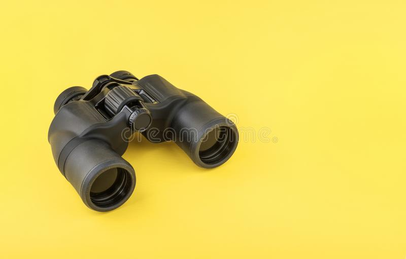 Binoculars on yellow background royalty free stock images