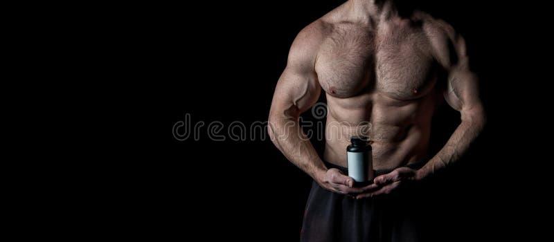 Bio benefícios aditivos O torso com seis blocos olha atrativo no fundo preto Torso muscular com músculos enormes imagens de stock