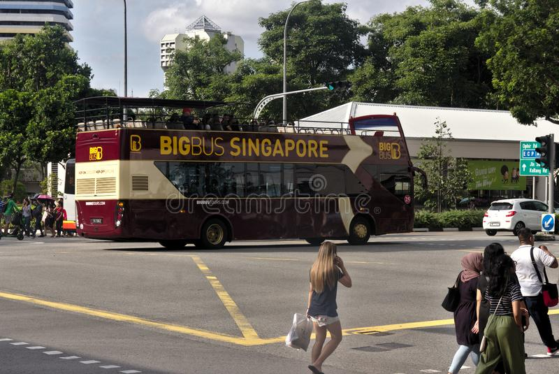 Bio buss med turister som är onboard i i stadens centrum Singapore med den korsningen för några gångare royaltyfria foton