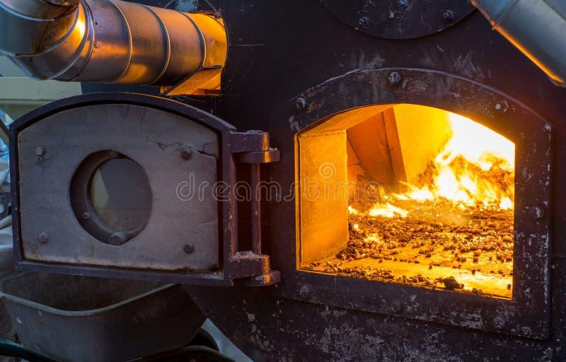 Bio combustible ardiente de las pelotillas en la caldera Económico, combustible del ecologicla imagenes de archivo