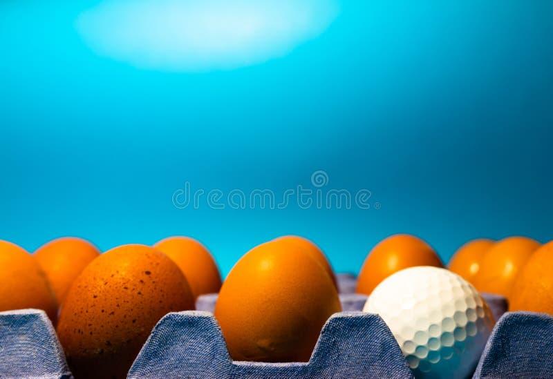 Bio-Eier, die in einem Rack aus blauem Pappe sitzen, wobei ein Ei durch einen Golfball ersetzt wird Konzept, aus der Menge heraus stockfotografie
