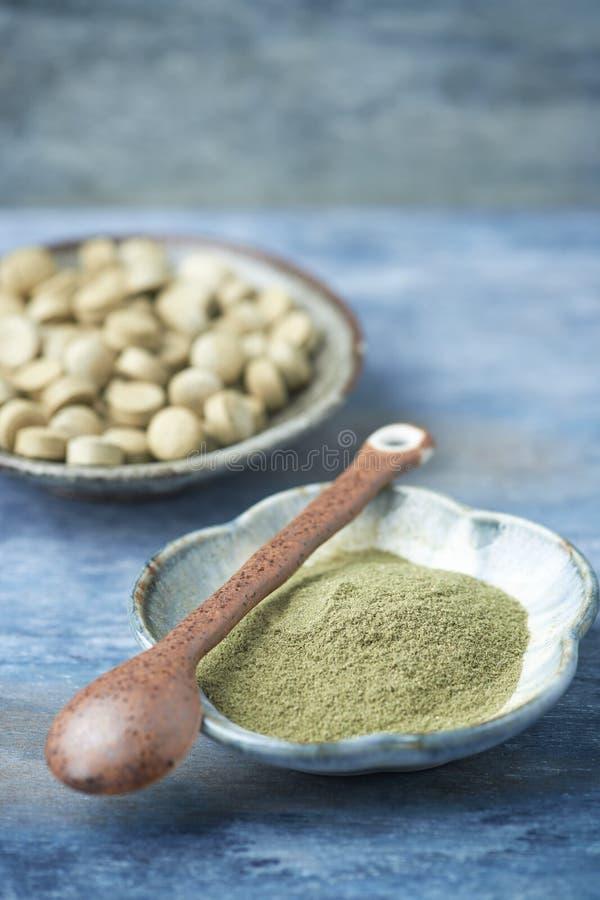 Bio gröna pulver och minnestavlor för KORNGRÄS Begrepp för ett sunt diet-tillägg arkivfoton