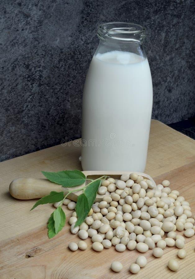 Bio leite de soja de derramamento no fundo escuro de madeira rústico foto de stock