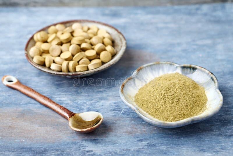 Bio p? e tabuletas verdes da GRAMA de CEVADA Conceito para um suplemento diet?tico saud?vel foto de stock