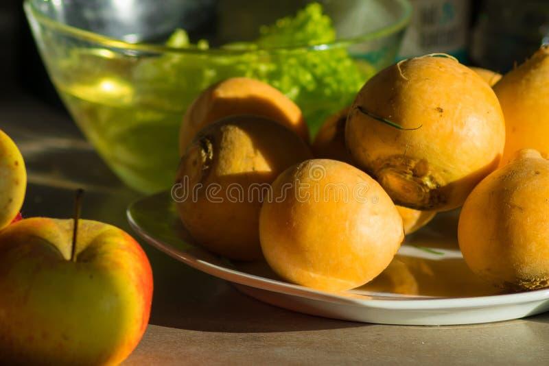 Bio- rapa gialla sul piatto con la mela e l'insalata fotografie stock libere da diritti