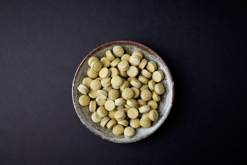 Bio tabletas verdes de la HIERBA de CEBADA Concepto para una suplementaci?n diet?tica sana foto de archivo
