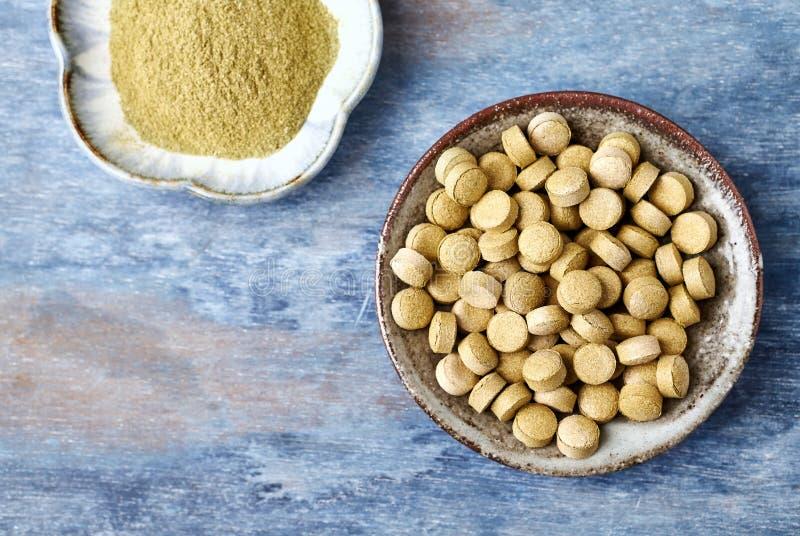 Bio tabletas y polvo verdes de la HIERBA de CEBADA Concepto para una suplementaci?n diet?tica sana imagenes de archivo