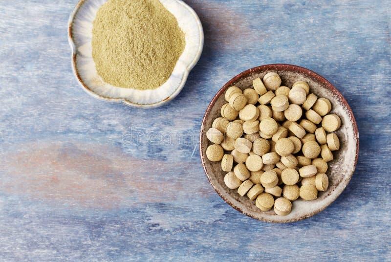 Bio tabuletas e p? verdes da GRAMA de CEVADA Conceito para um suplemento diet?tico saud?vel fotos de stock