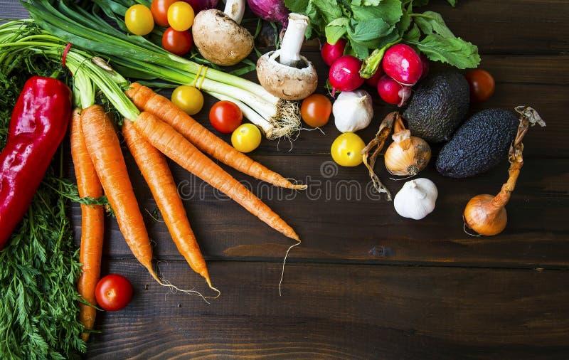 Bio vegetais orgânicos saudáveis com cenouras, verdes, cebola, avocads, tomates, cogumelos, bio colheita verde fresca fotos de stock royalty free
