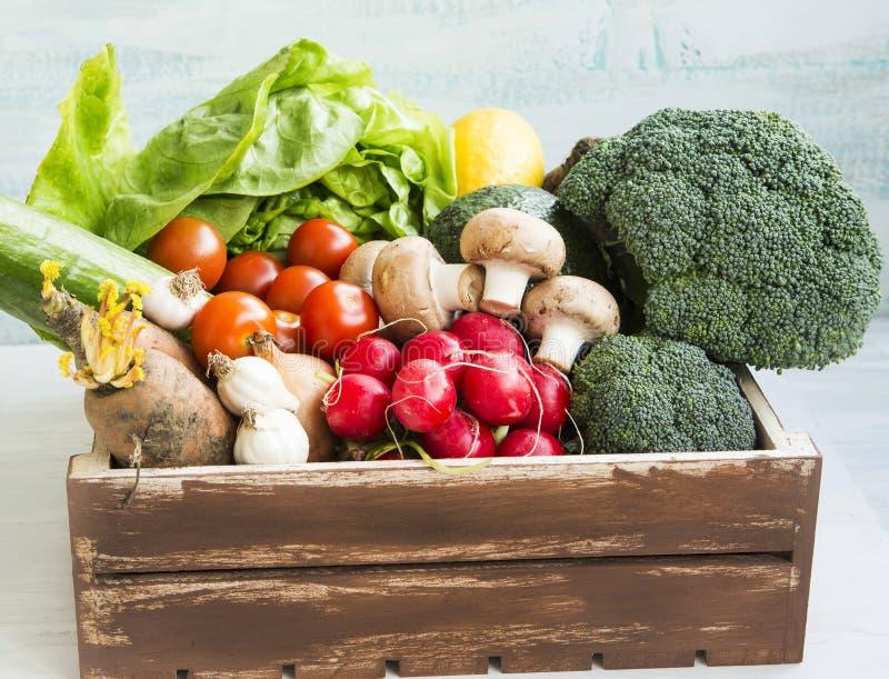 Bio verduras frescas en cajón de madera con el rábano, ensalada, setas, bróculi, tomates imagen de archivo