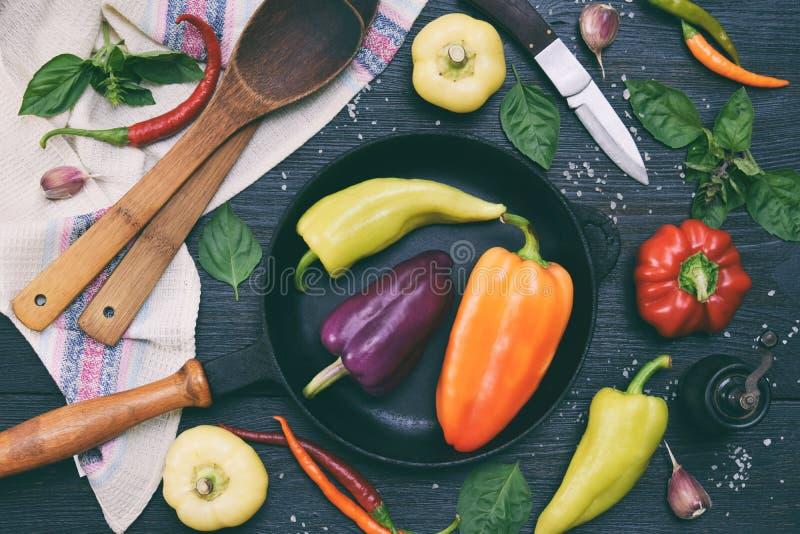 Bio- verdure fresche organiche di estate - varietà differenti di dolce e di peperoncini su fondo di legno scuro Ingredienti per i immagini stock libere da diritti