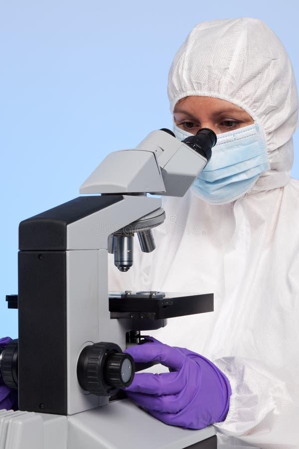 Biochemicus die door een microscoop kijkt stock foto's