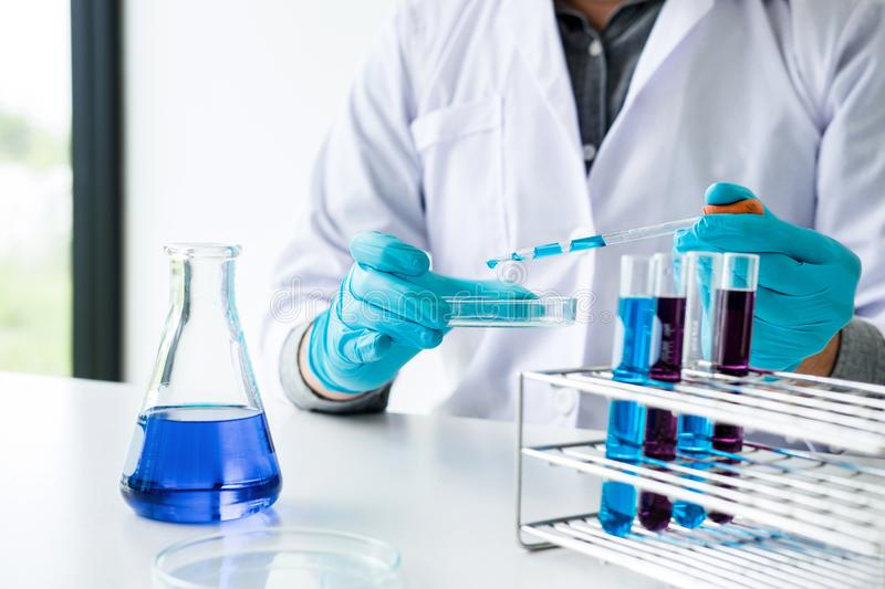 Biochemistry laboratory research, Scientist or medical in lab coat holding test tube with reagent with drop of color liquid over stock photo