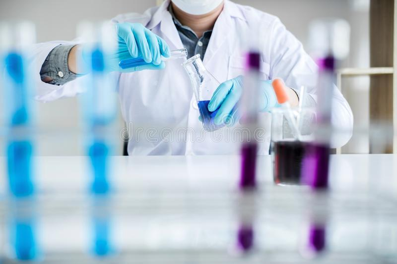 Biochemistry laboratory research, Scientist or medical in lab coat holding test tube with reagent with drop of color liquid over stock photos