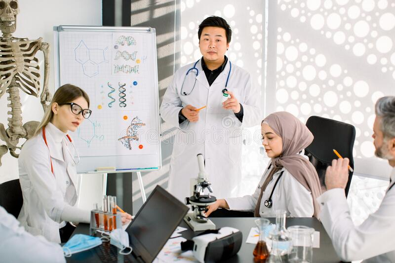 Biochemistry, pharmacology, drug industry, clinical trials. Young Asian doctor talks about the results of clinical trial. Of new medicine, having a meeting with stock photography