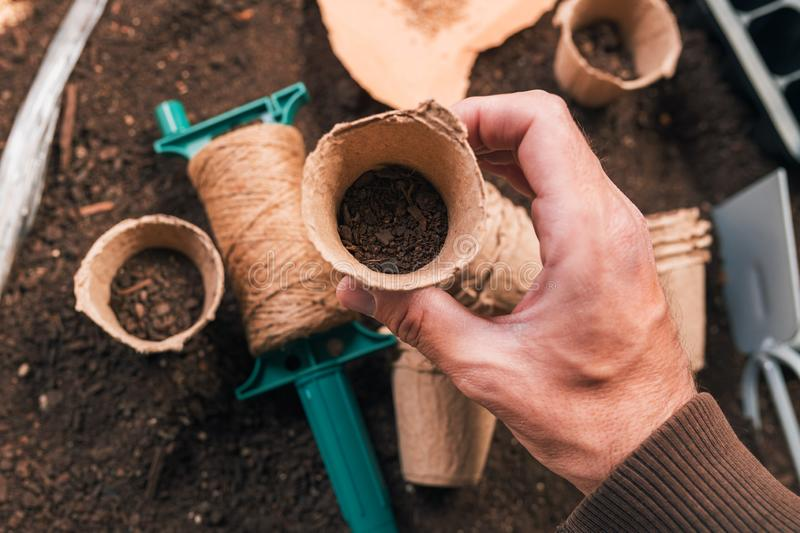 Biodegradable cardboard planting pot in hand of male gardener royalty free stock photography