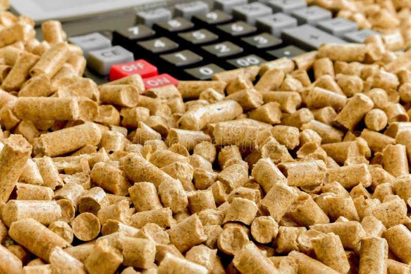 Biofuels, Milieuvriendelijke brandstof Alternatieve biofuel van zaagsel voor het branden in ovens Houten korrels en calculator royalty-vrije stock foto's
