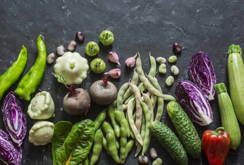 Biogartengemüse-Lebensmittelhintergrund Rotkohl, Zucchini, Pfeffer, rote Rüben, Bohnen, Kürbisse, Knoblauch auf dunklem Hintergru stockfoto