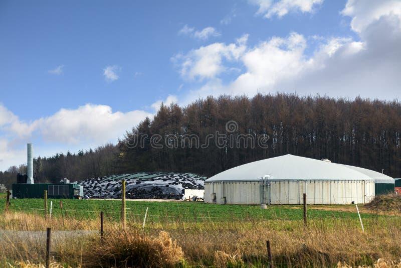 Biogasväxt för förnybara energikällor mellan fältet och skogen, bl royaltyfri fotografi