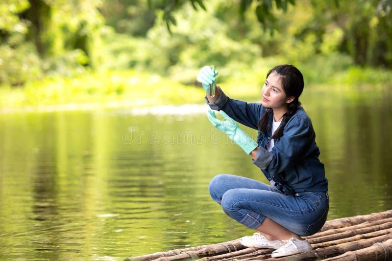 Biología estudiantil asiática tomando y probando muestras de agua natural del río. Expertos científicos mujeres guardan agua p foto de archivo libre de regalías