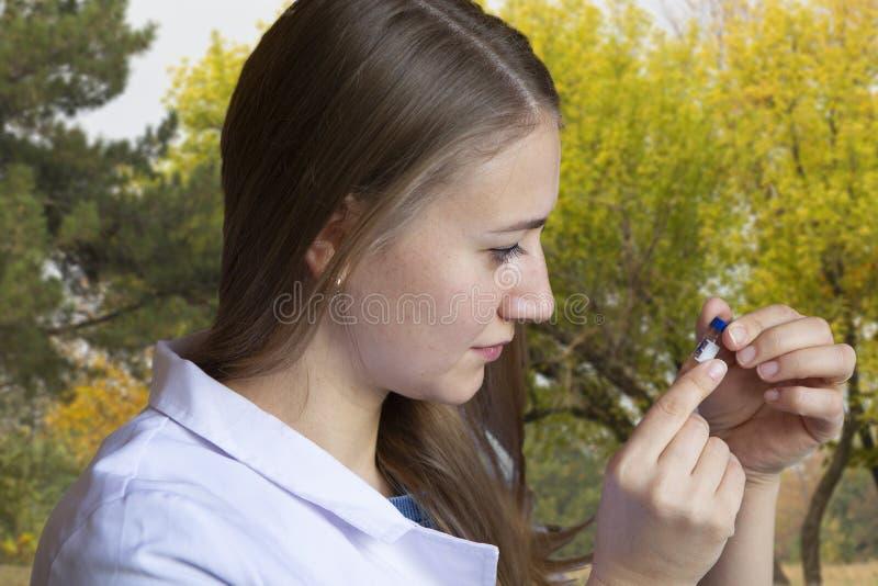 Biolog för ung kvinna i hällande flytande för vitt lag från provröret in i krukan med jord Groddar i bakgrund i växthus royaltyfria bilder