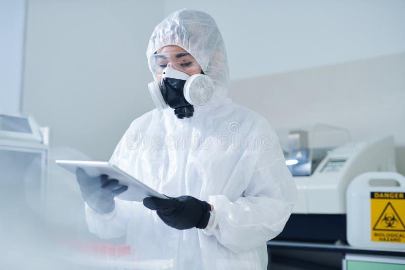 Biologe im schützenden Kostüm unter Verwendung der Tablette stockfotos