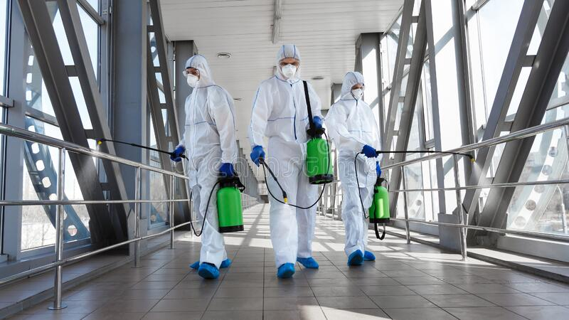 Men in a protective suit and mask disinfecting tunnel with gas. Biological hazard. Epidemic of the coronavirus. Men in a protective suit and mask disinfecting stock photography