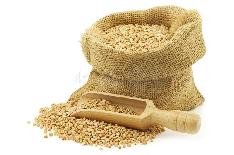 Biologically grown organic buckwheat in a burlap bag with a wooden scoop. On a white background royalty free stock photos