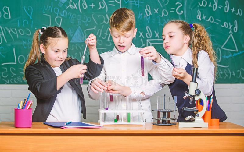 Biologieonderwijs Kleine jonge geitjes die chemie in laboratorium leren studenten die biologieexperimenten met microscoop in labo stock afbeeldingen