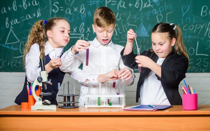 Biologieonderwijs Kleine jonge geitjes die chemie in laboratorium leren studenten die biologieexperimenten met microscoop in labo stock foto's
