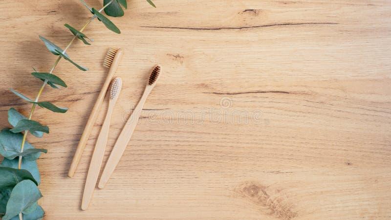 Biologisch abbaubare ökologisch verträgliche Bambuskohle-Zahnbürste und grünes Eukalyptus-Leaf auf Holztisch Topansicht mit Kopie lizenzfreie stockbilder
