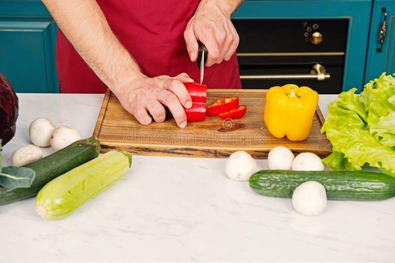 Biologische productenconcept De peper van de handplak met ceramisch mes Groenten worden die die op houten scherpe raad worden ges royalty-vrije stock afbeelding