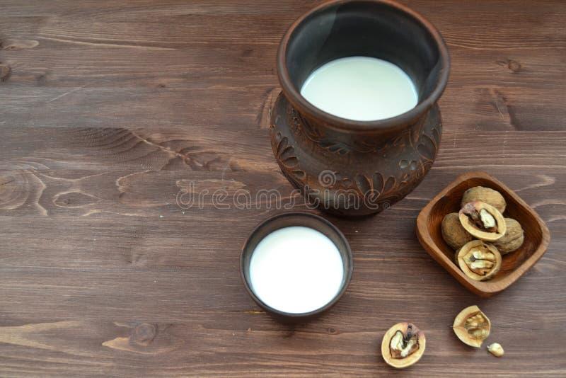 Biologisches Lebensmittel und Antioxydantkonzept: Milch und Walnüsse auf Holztisch mit Kopienraum lizenzfreies stockbild