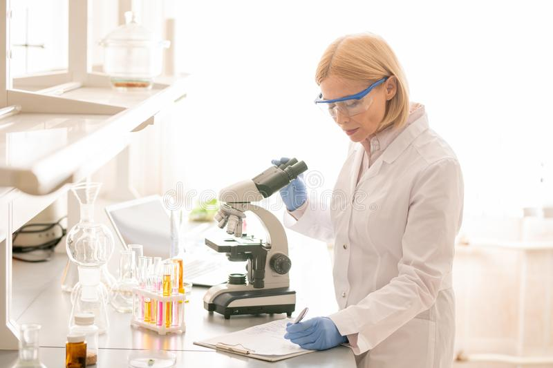 Biologist noting observations in laboratory. Serious concentrated lady biologist in lab coat and safety goggles using microscope and noting observations in royalty free stock photos