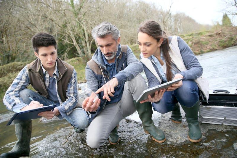 Biologiste avec des étudiants de biologie examinant l'eau de rivière images libres de droits