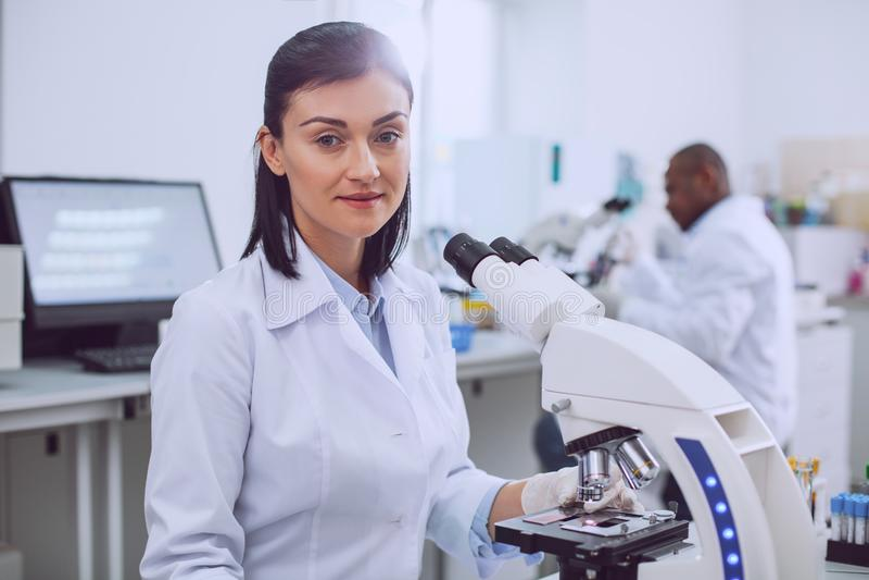 Biologiste féminin heureux travaillant dans le laboratoire images stock