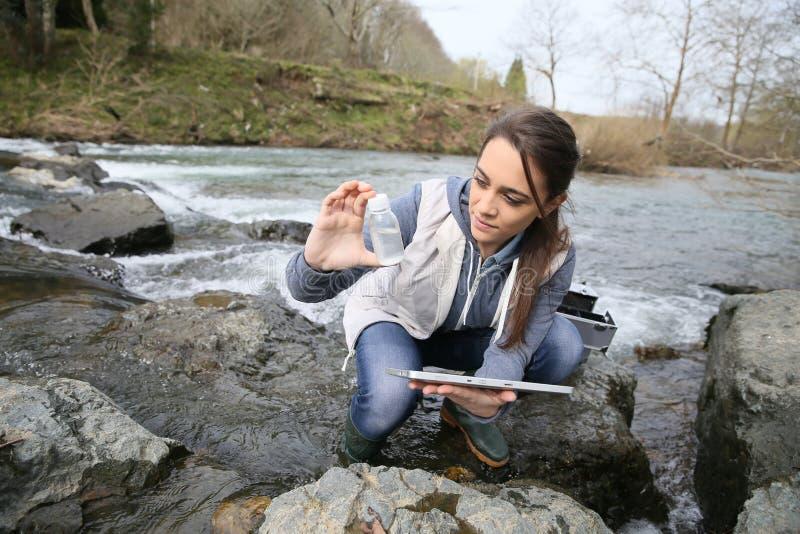 Biologistudent som tar en prövkopia från floden royaltyfri bild