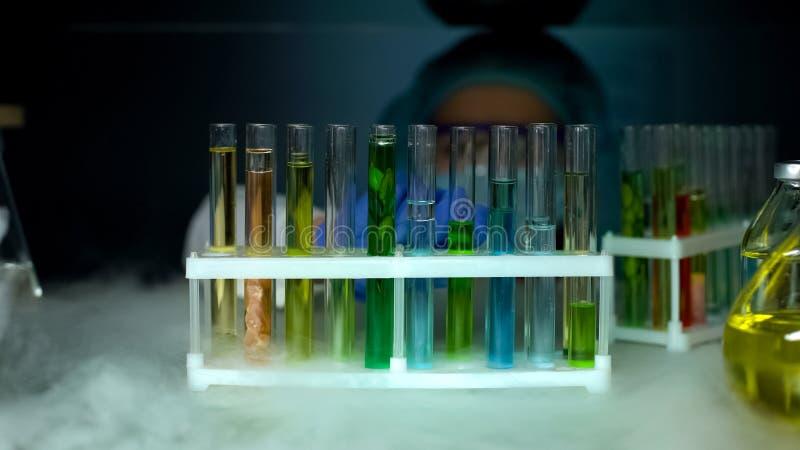 Biologo che esamina le provette con i campioni in frigorifero, lavoro di laboratorio fotografia stock