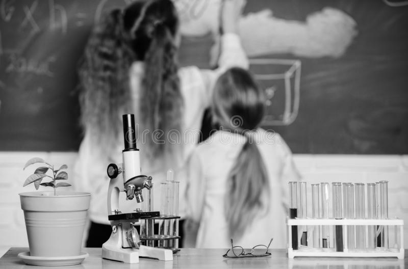 Biology concept. Microscope and test tubes on table in classroom. Kid near school chalkboard background defocused royalty free stock photography