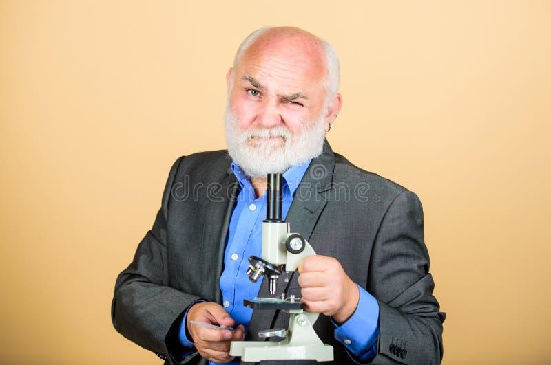 Biology education. science lab. chemistry in school laboratory. mature bearded teacher with microscope. senior man stock image
