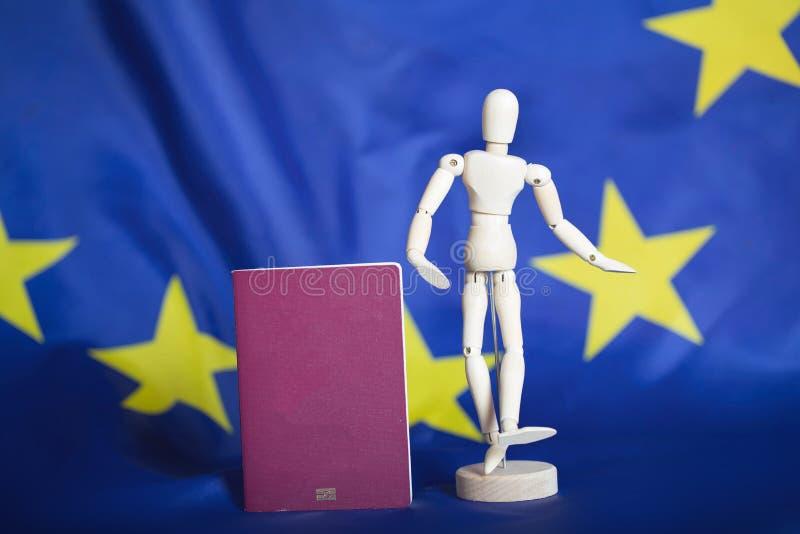 Biometric passport and dummy figurine in front go EU flag. Biometric passportand dummy figurine in front go EU flag. Closeup stock images
