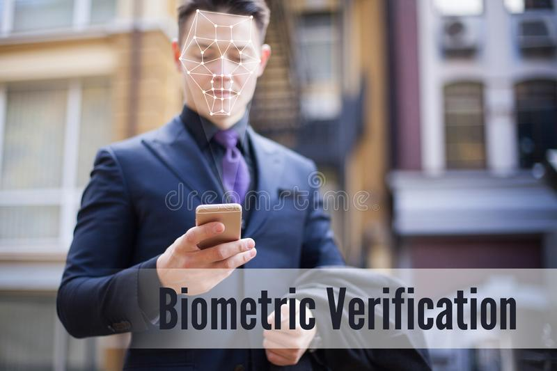 Biometric recognition of a person`s face. A man in a business suit is looking at the phone. Face ID stock photo