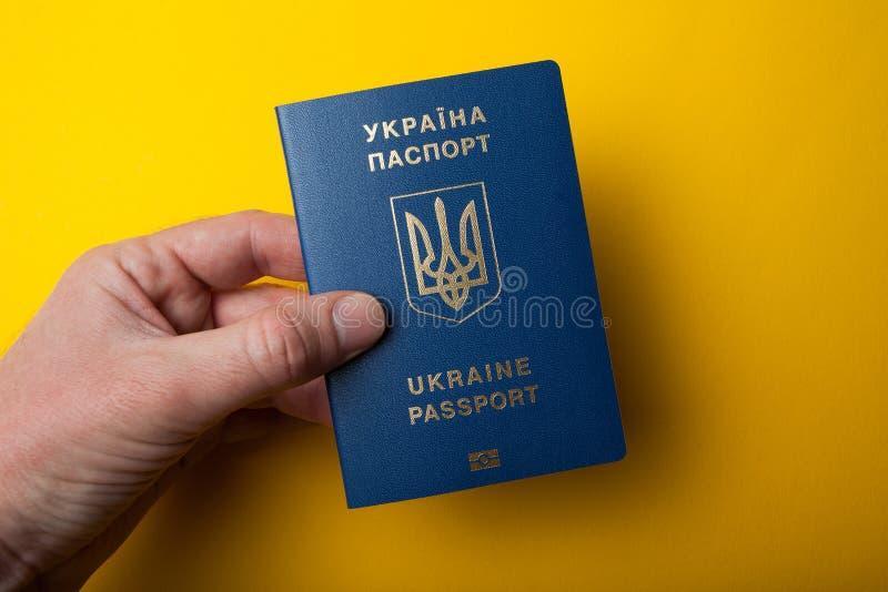 Biometric ukrainskt pass i hand på en gul bakgrund arkivfoto