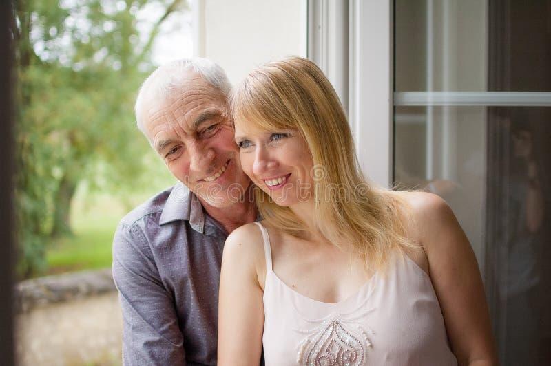 Bionda abbastanza bella che sta vicino alla finestra con il suoi marito e sorridere senior Concetto di differenza di età immagine stock