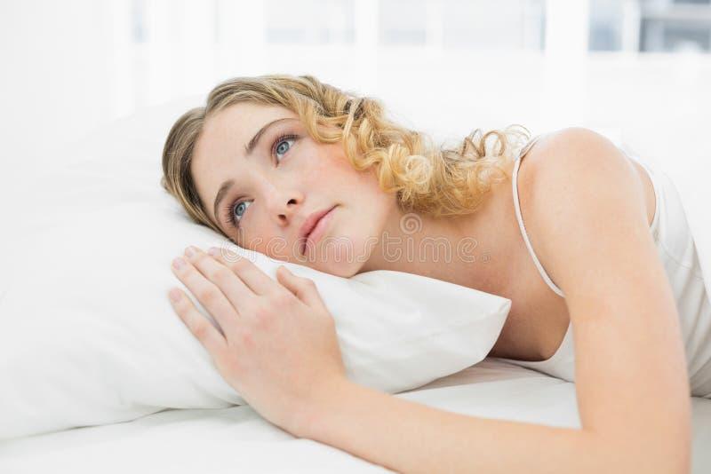 Bionda abbastanza calma che si trova a letto cercare di riposo immagini stock libere da diritti