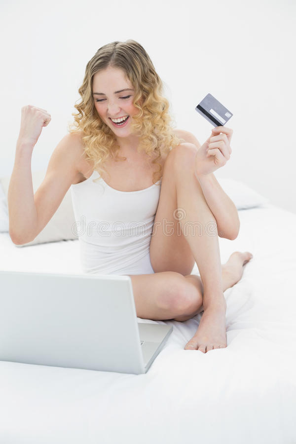 Bionda abbastanza emozionante che si siede sul letto facendo uso del computer portatile e della carta di credito fotografie stock